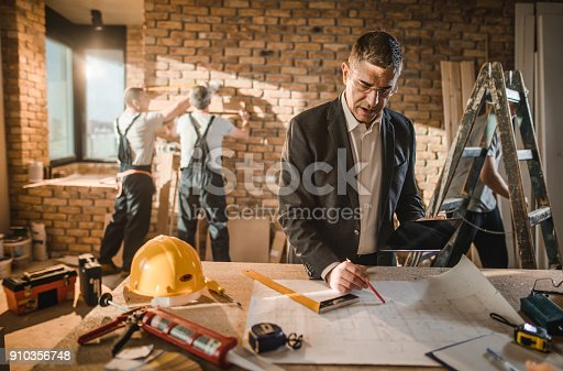 512113530 istock photo Mid adult male architect going through housing plan at construction site. 910356748