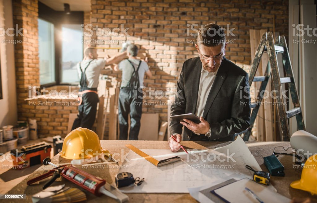 Mid adult male architect going through housing plan at construction site. stock photo