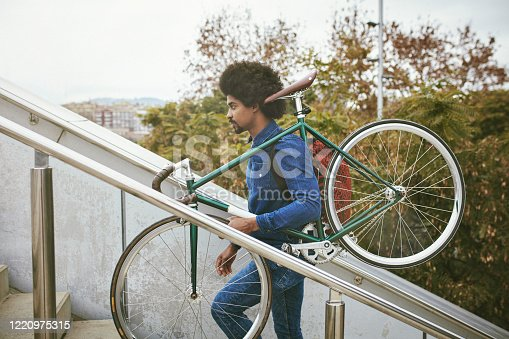 Side view of Afro-Caribbean man in early 30s wearing casual denim clothing and carrying bicycle up outdoor staircase on way home from work.