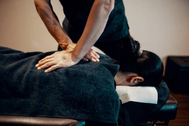 mitteler erwachsener männlicher chiropraktiker, der eine patientin behandelt - chiropraktik wellness stock-fotos und bilder