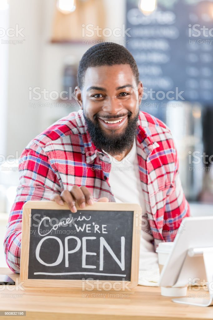 Mid adult male coffee shop owner displays open sign for camera stock photo