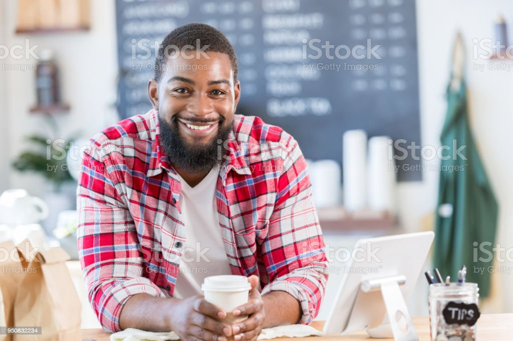 Mid adult male coffee shop owner smiles proudly for camera stock photo