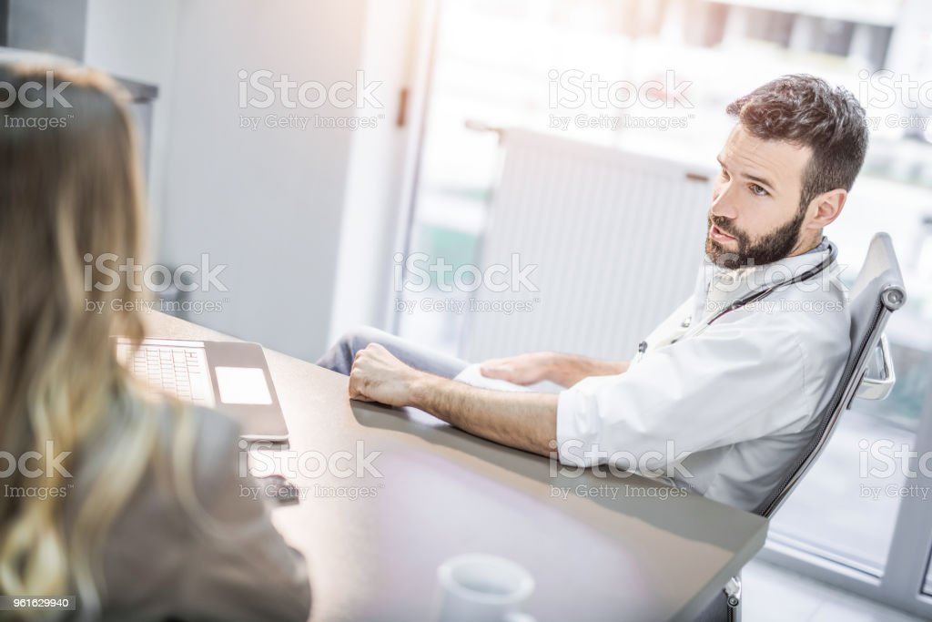 Mid adult male doctor having a visit from young female patient. stock photo