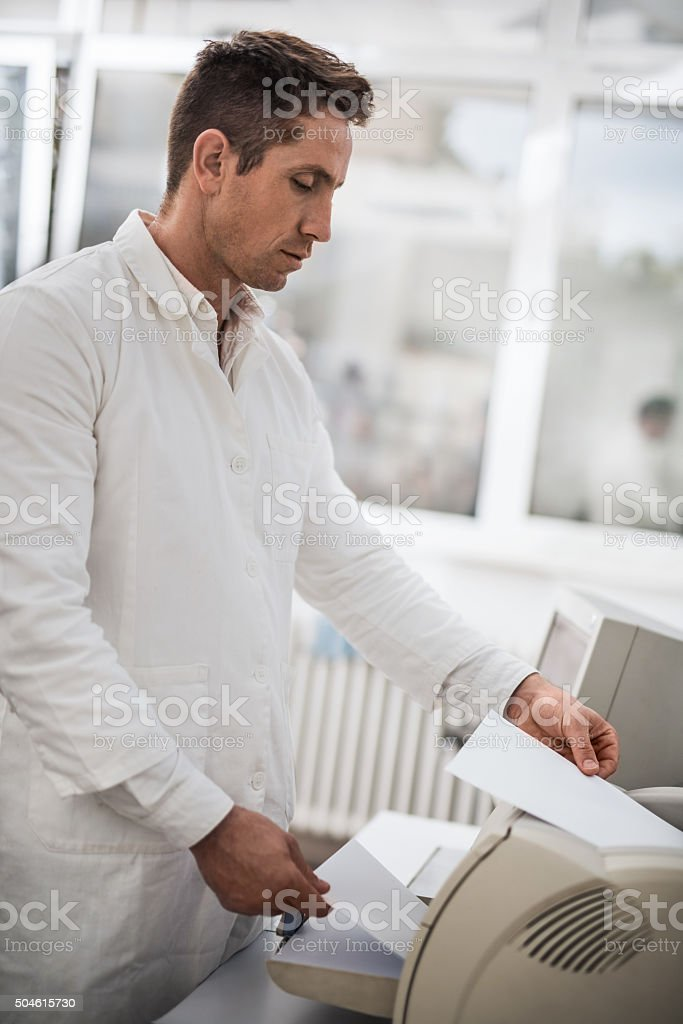 Mid adult male doctor printing papers on computer printer. stock photo