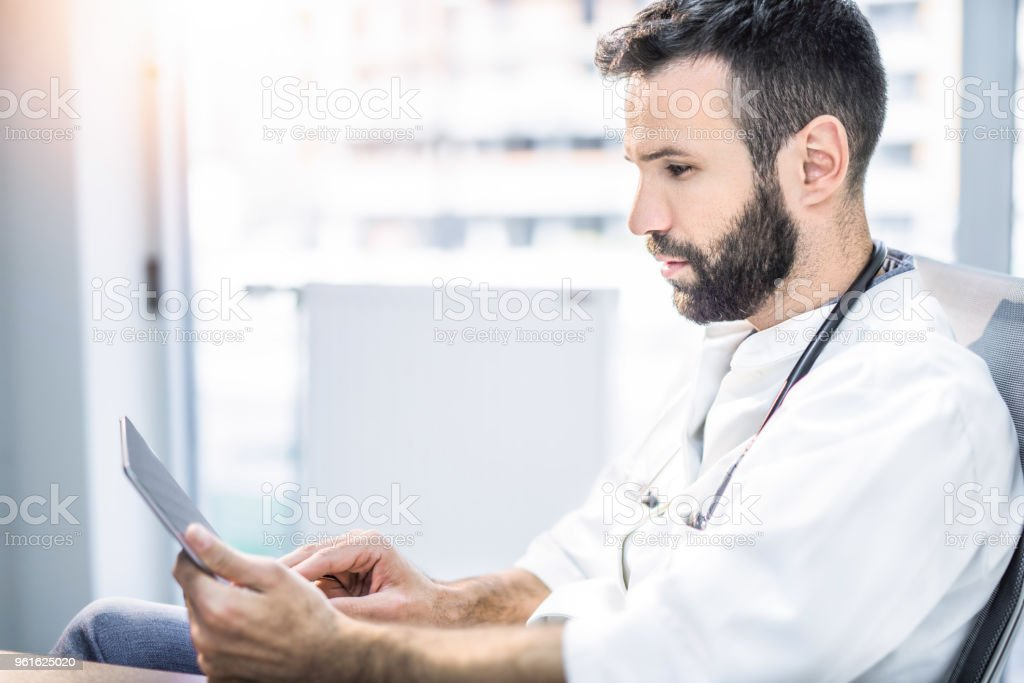 Mid adult male healthcare worker in digital age. stock photo