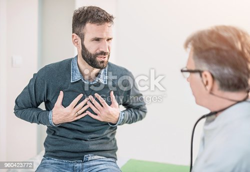 Mid adult male patient describing a chest pain to his doctor.