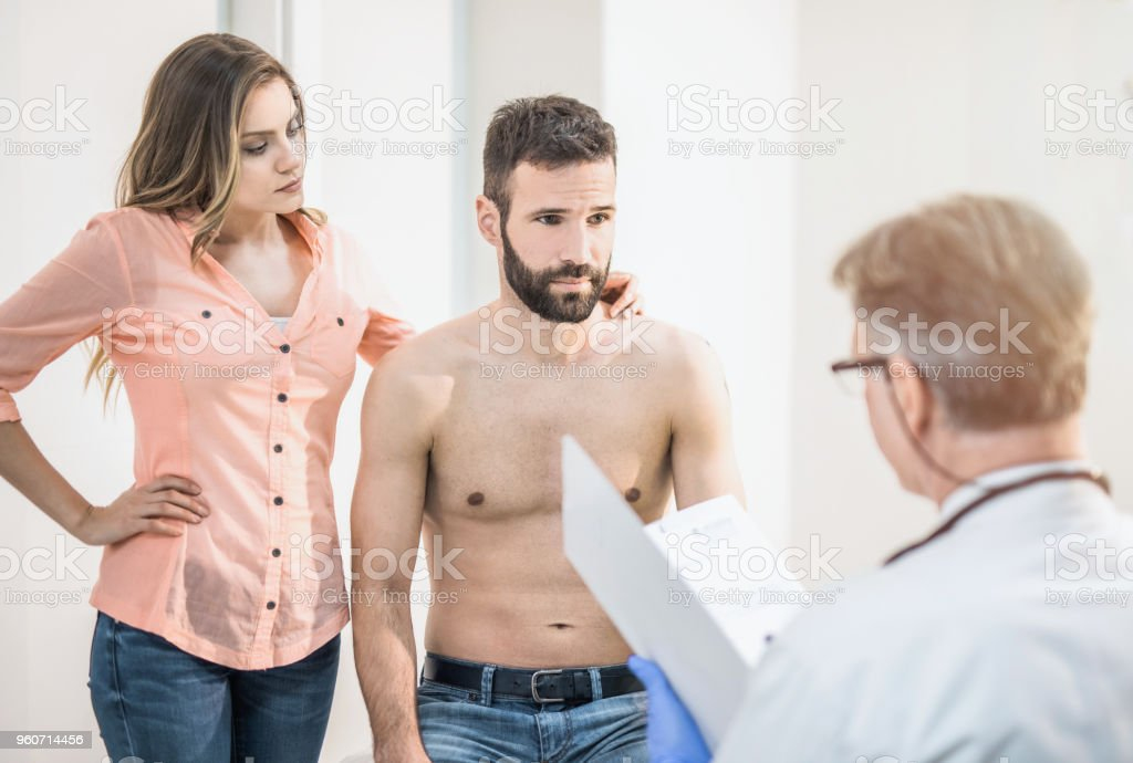 Mid adult male patient visiting a doctor with his wife. stock photo
