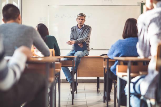 mid adult male teacher giving a lecture to his students in the classroom. - professore di scuola superiore foto e immagini stock