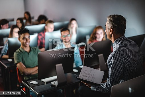 Male teacher talking to large group of students on a class at computer lab.