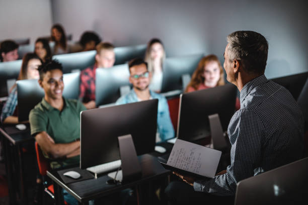 Mid adult male teacher teaching the lecture in computer lab. stock photo