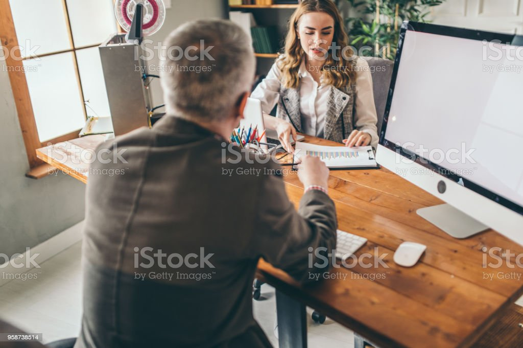 Mid adult man and young woman working in the office stock photo