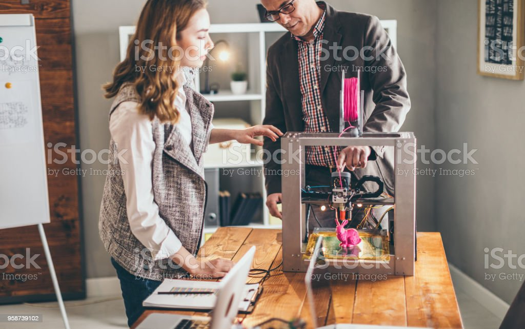 Mid adult man and young woman working on 3d printer stock photo