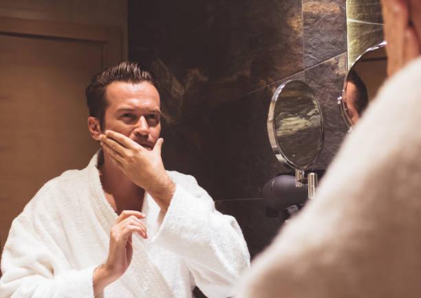 Mid adult man applying face cream in the bathroom.