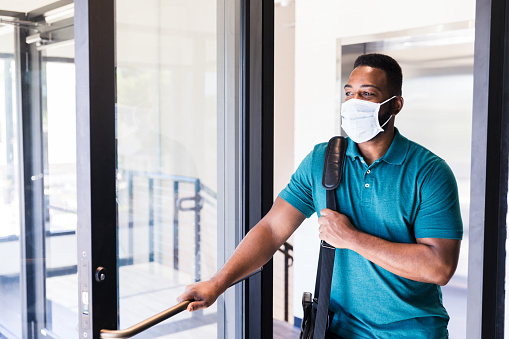 The mid adult man arrives at work wearing a protective mask because of the coronavirus epidemic.