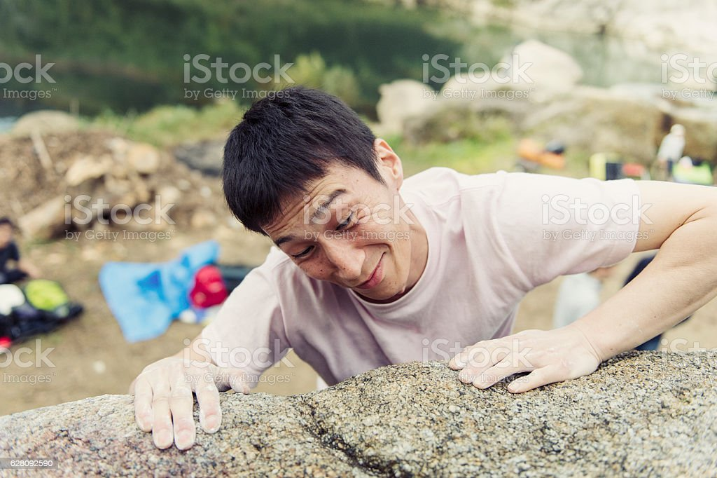Mid adult man challenging rock climbing stock photo