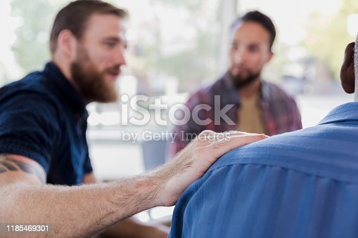 956725746 istock photo Mid adult man comforts friend during therapy sesion 1185469301