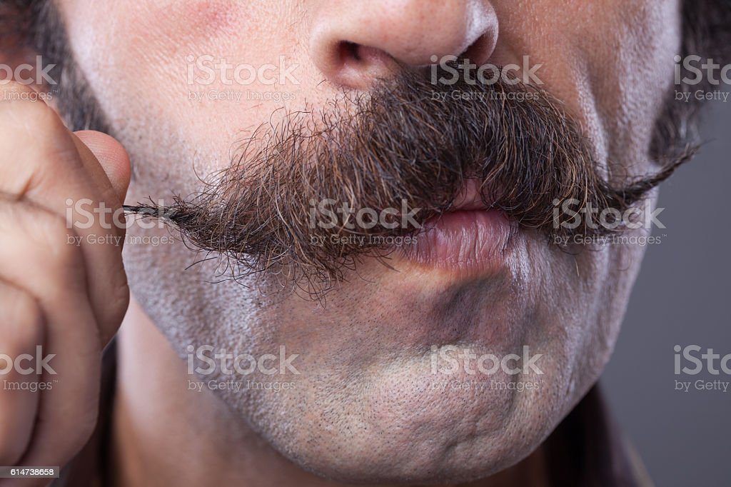 Mid adult man curling up his handle bar mustache stock photo
