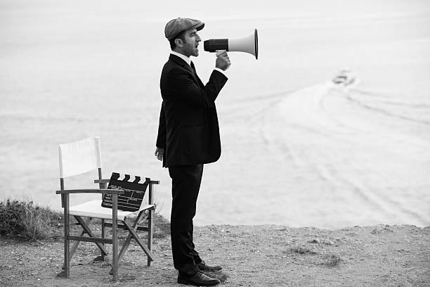 mann mittleren alters regeln film im outdoor-film - klappe hut stock-fotos und bilder