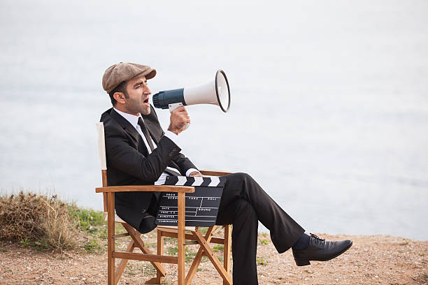 mid adult man directing film in outdoor set - director stock photos and pictures