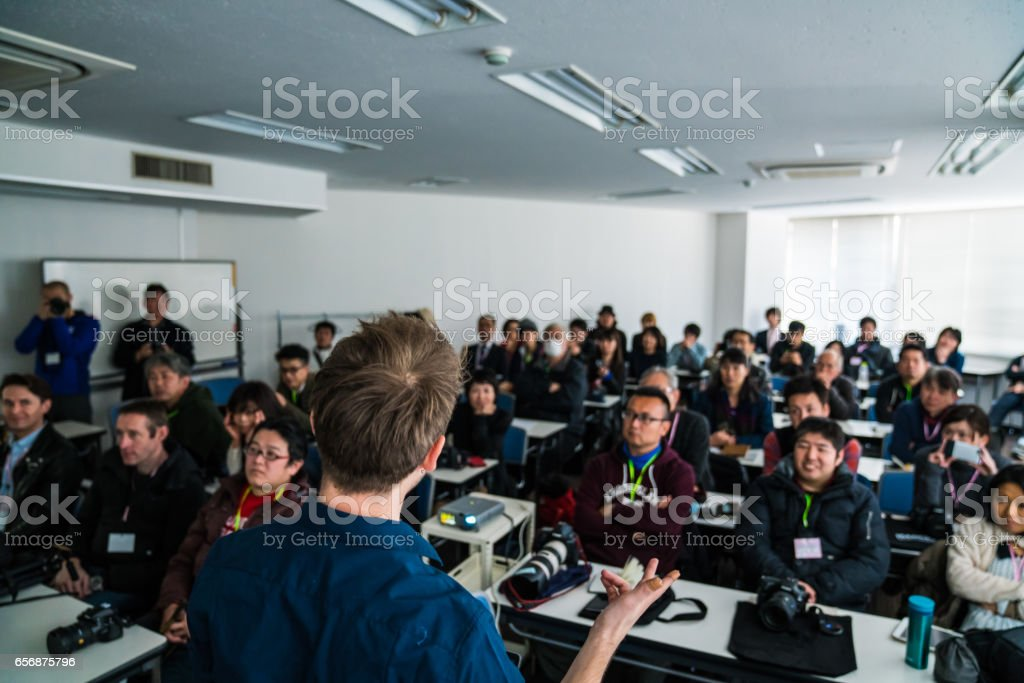 Mid adult man giving a presentation or speech to a large group of people stock photo