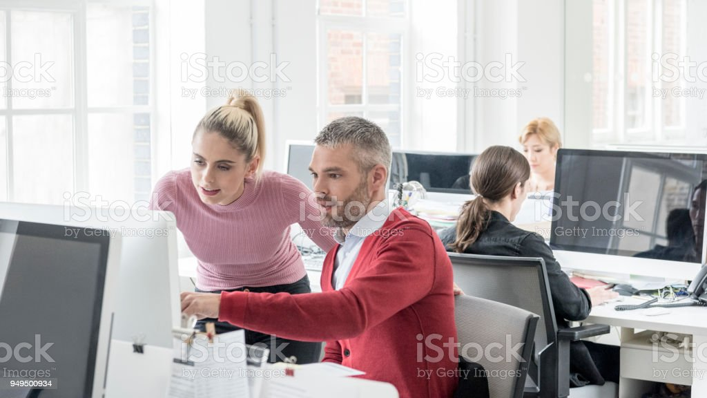Mid adult man in red cardigan using computer with female colleague assisting stock photo
