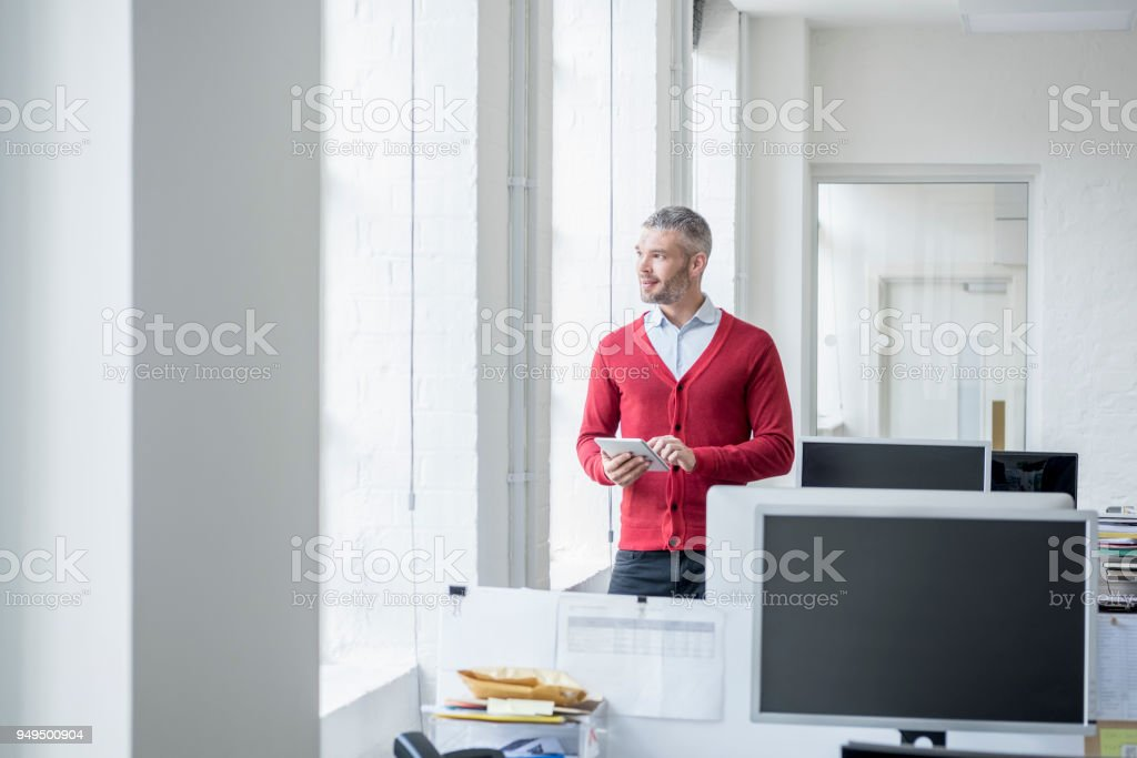 Mid adult man in red cardigan using tablet and looking out of window stock photo