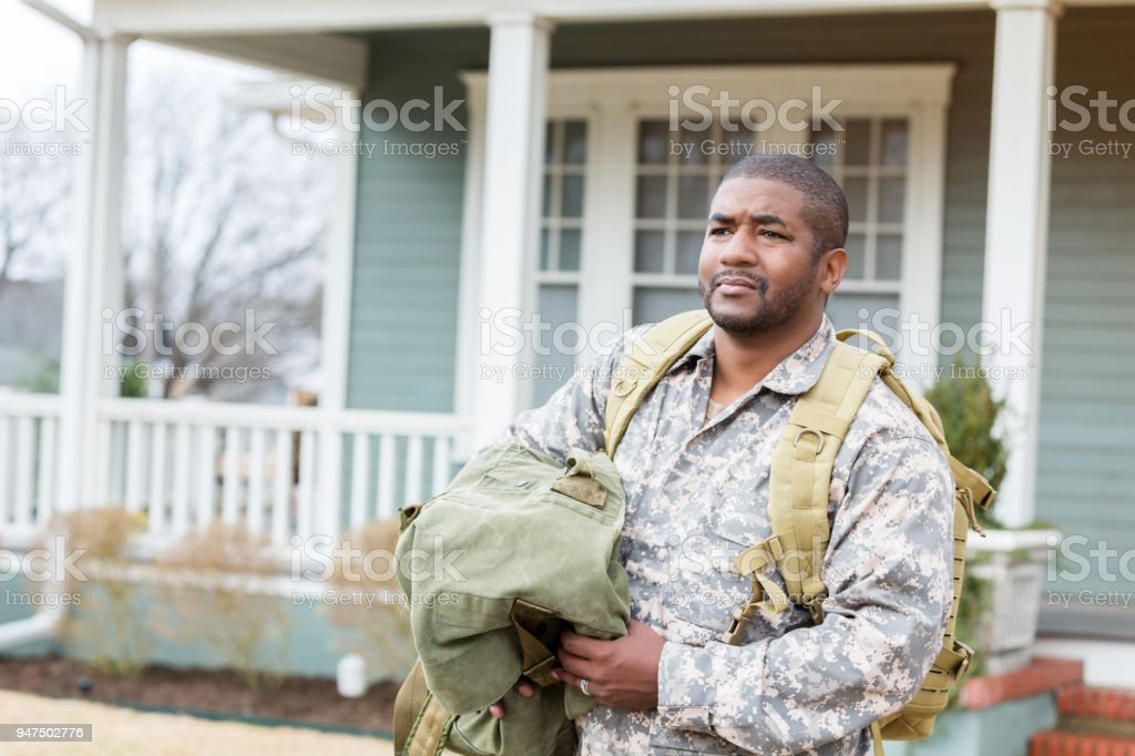 Mid adult man is sad to leave for military deployment stock photo