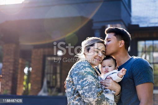 While standing in their front yard, a mid adult husband kisses his soldier wife before she leaves for an assignment. The woman is holding their baby girl.