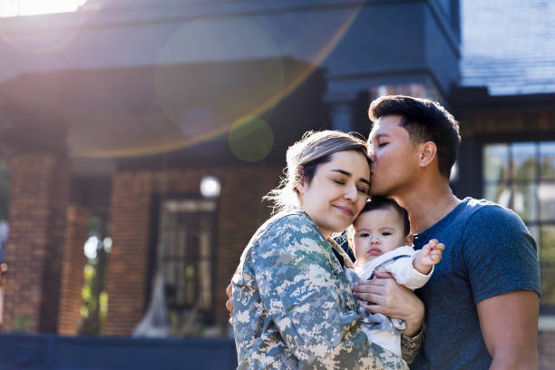 Mid adult man kisses his soldier wife While standing in their front yard, a mid adult husband kisses his soldier wife before she leaves for an assignment. The woman is holding their baby girl. husband stock pictures, royalty-free photos & images