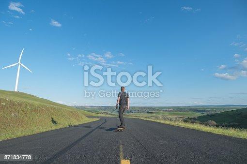 istock Mid adult man longboards down rural highway 871834778