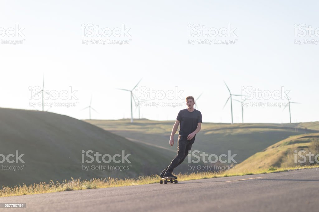 Mid adult man longboards down rural highway surrounded by wind turbine farm stock photo