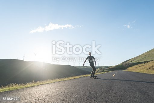 istock Mid adult man longboards down rural highway surrounded by wind turbine farm 871834772