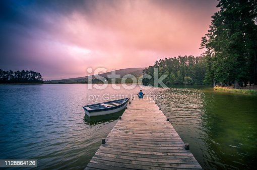 Wide shot of a 40-44-year-old Caucasian man sitting cross-legged meditating on a wooden jetty on a full lake of water overlooking mountains and woodlands with a moored rowboat with a dramatic purple orange coloured mood Cape Winelands South Africa