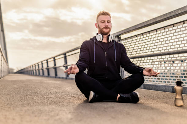Mid adult man meditating on the bridge in the early morning. stock photo