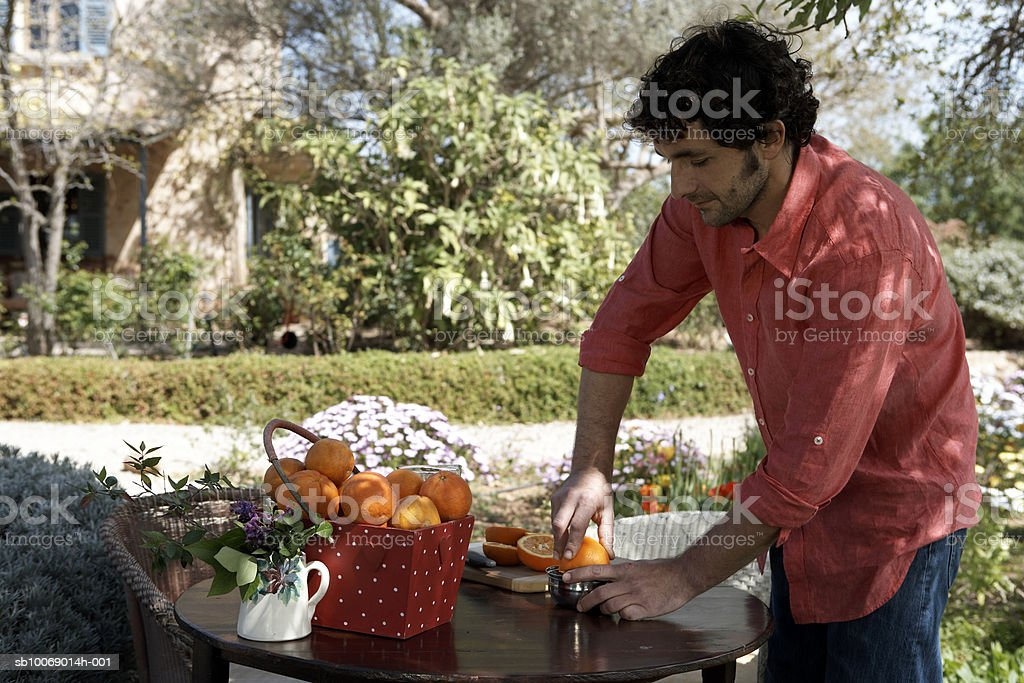 Mid adult man preparing orange juice in garden 免版稅 stock photo