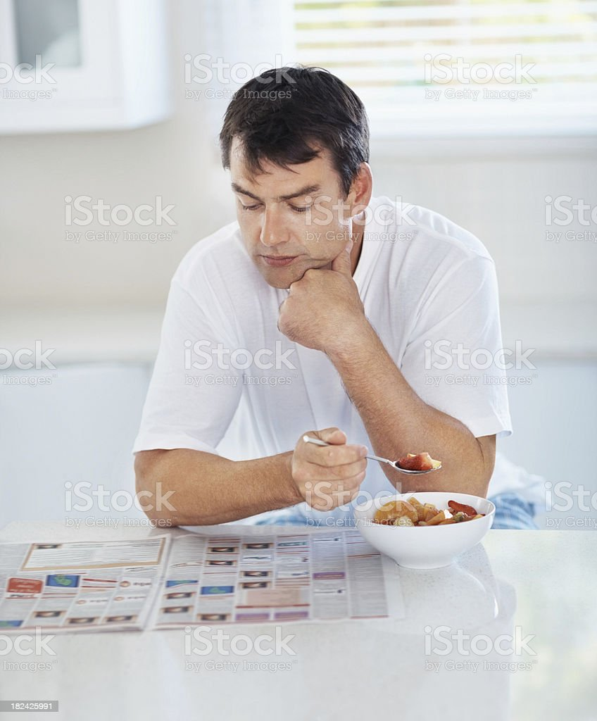 Mid adult man reading newspaper while having breakfast royalty-free stock photo