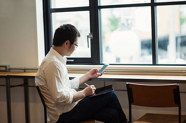 Mid adult man relaxing and working in a cafe stock photo