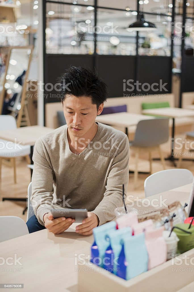 Mid adult man relaxing in a cafe. stock photo