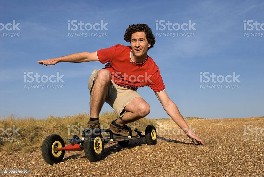 Mid adult man riding skateboard, looking away, smiling royalty-free stock photo
