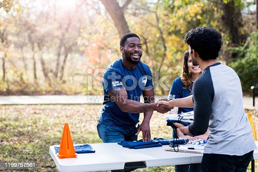 After getting him registered, the mid adult man shakes hands with the unrecognizable volunteer.