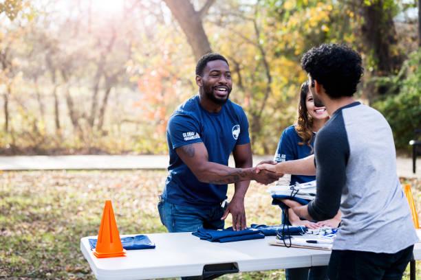 mid adult man shakes hands with unrecognizable volunteer - organizzazione no profit foto e immagini stock