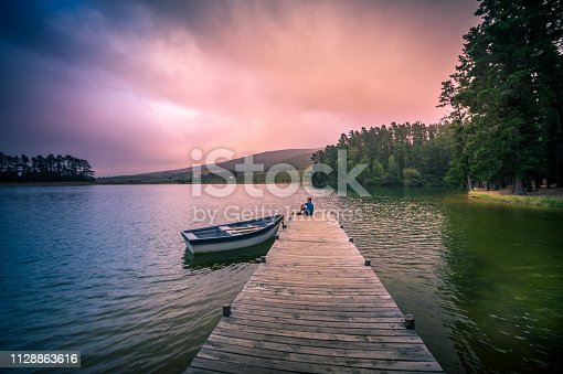 Wide shot of a 40-44-year-old Caucasian man on a wooden jetty on a full lake of water overlooking mountains and woodlands with a moored rowboat with a dramatic purple orange coloured mood Cape Winelands South Africa