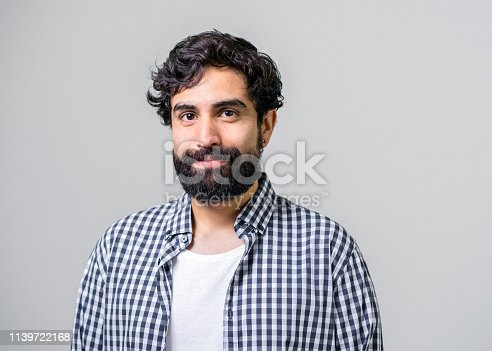 Portrait of mid adult man smiling on gray background. Handsome male is having beard. Hipster is wearing casuals.