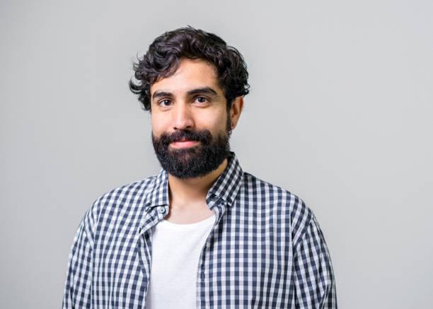 mitteler erwachsener mann lächelt auf grauem hintergrund - 30 34 jahre stock-fotos und bilder