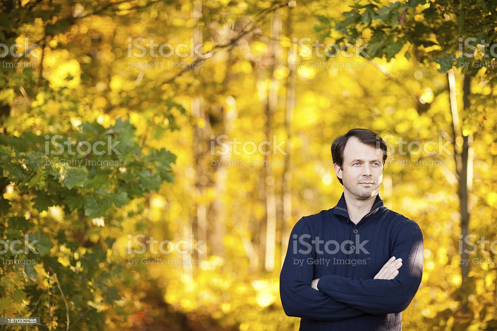 Mid Adult Man Standing in Colorful, Autumn Woods stock photo