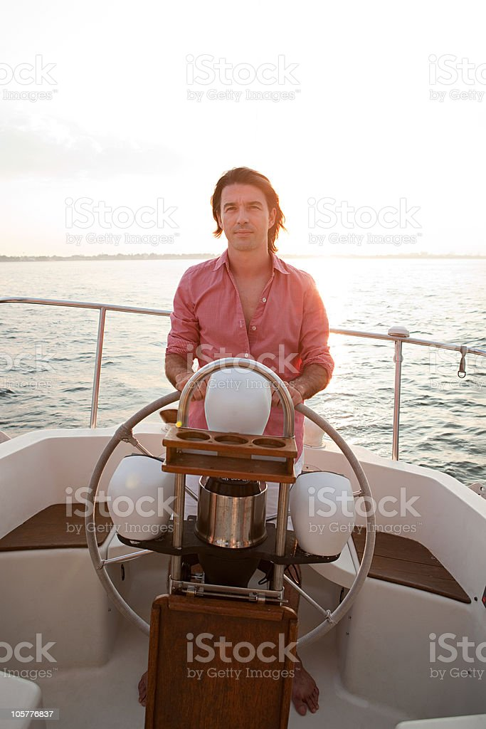 Mid adult man steering yacht royalty-free stock photo