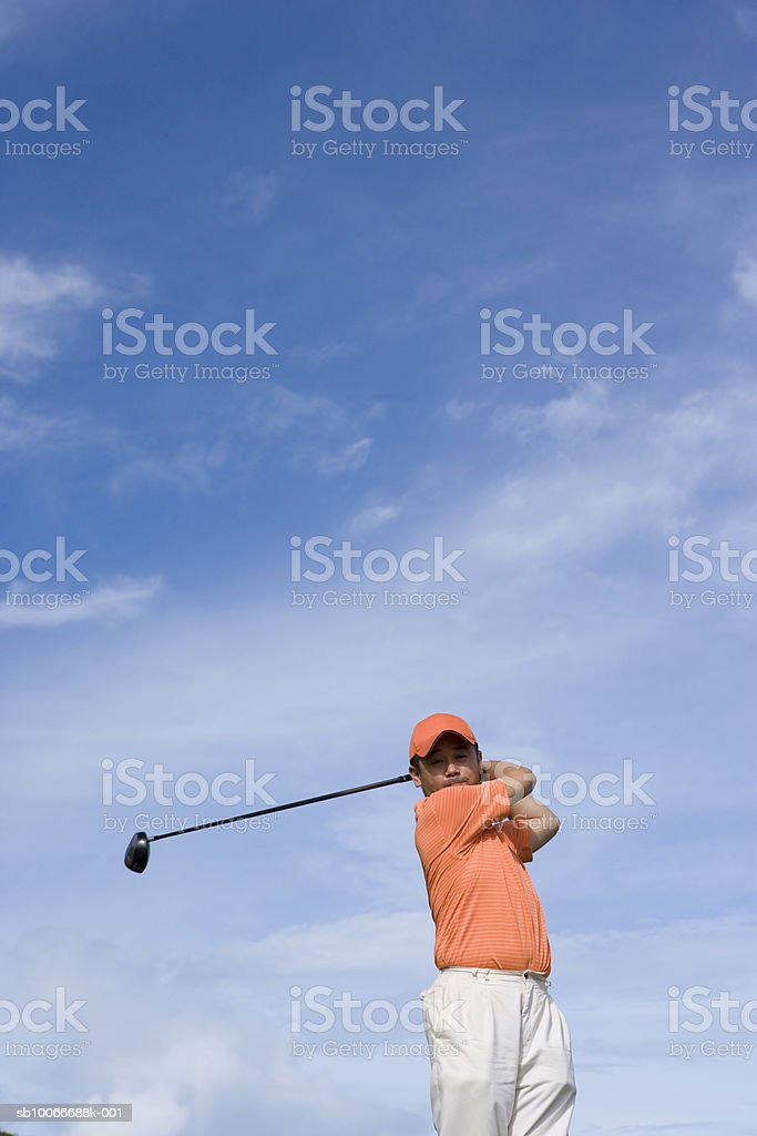 Mid adult man swinging golf club, low angle view royalty-free stock photo
