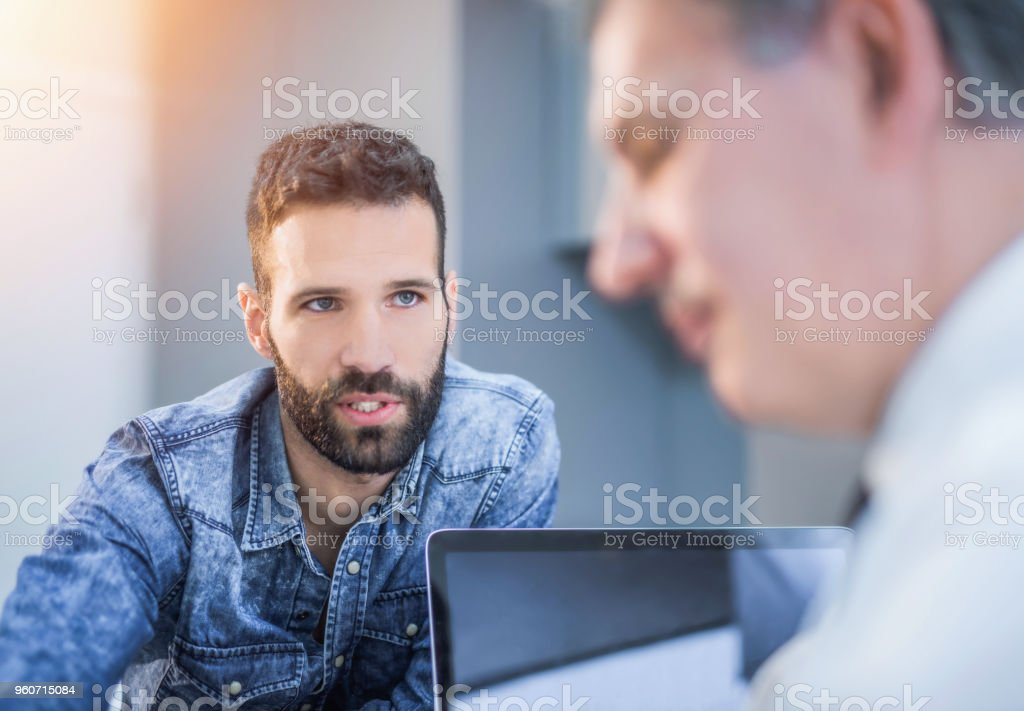 Mid adult man talking with his financial advisor. stock photo