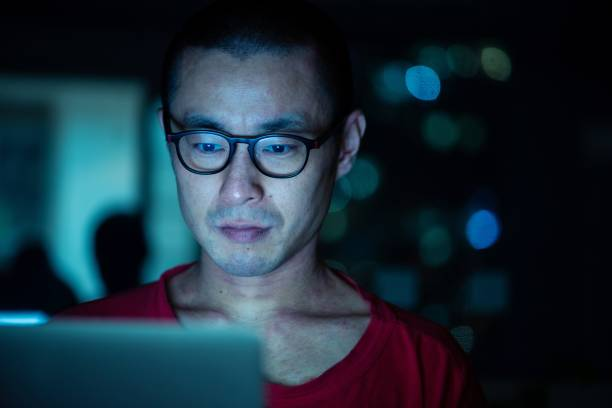 Mid adult man using a computer in the evening stock photo