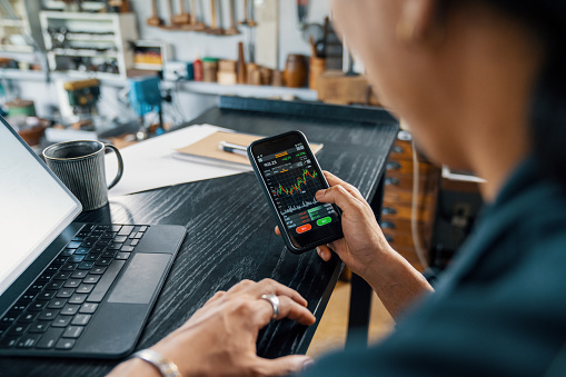 Mid adult man using a smart phone to monitor his cryptocurrency and stock trading. He is in his small jewellery workshop.